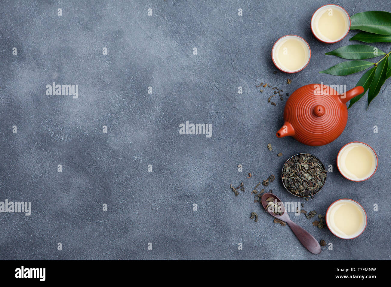 Green tea in tea pot and chawan bowls, cups on slate background. Top view. Copy space. Stock Photo