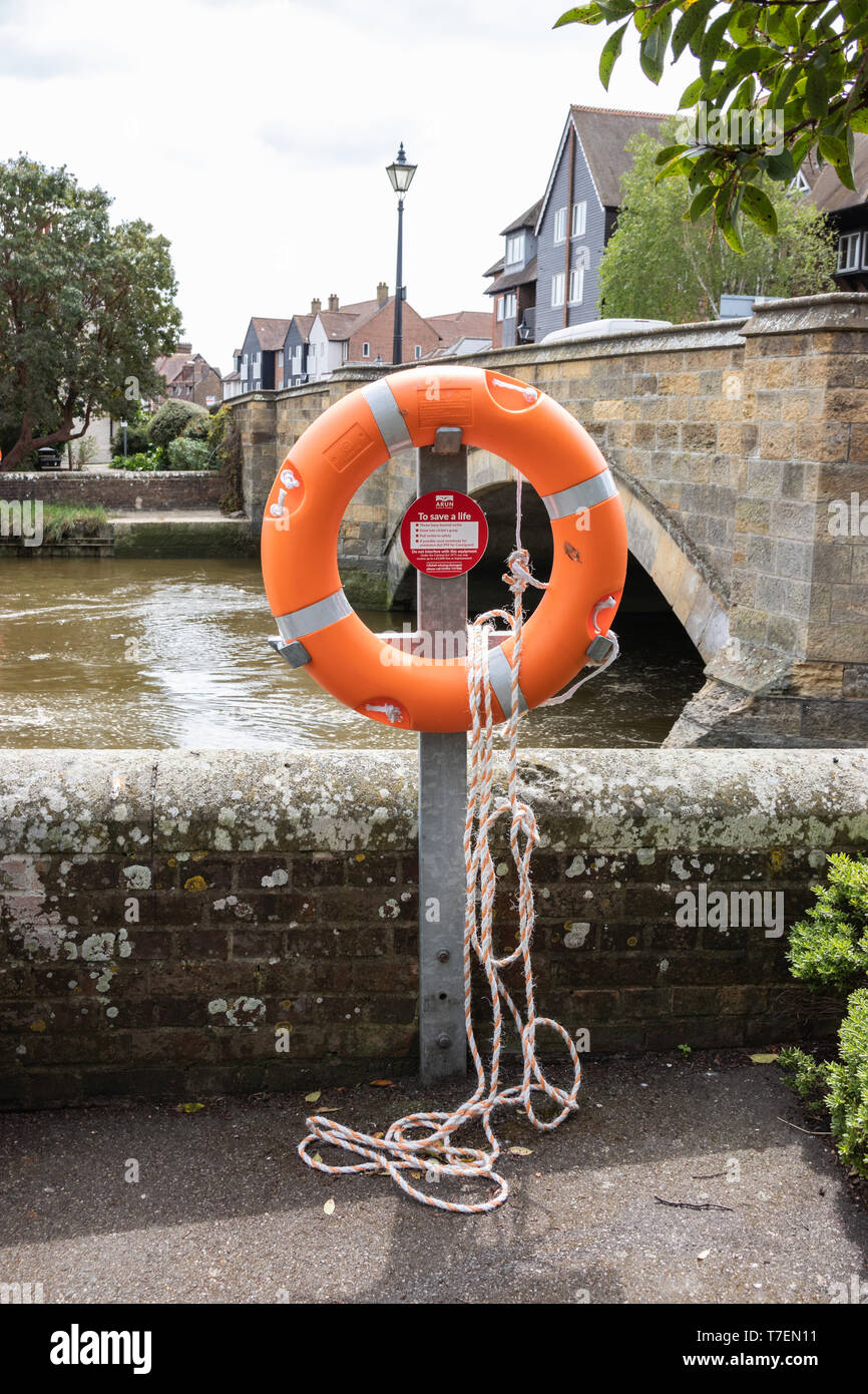 A life ring and rope on the side of a canal - Stock Image