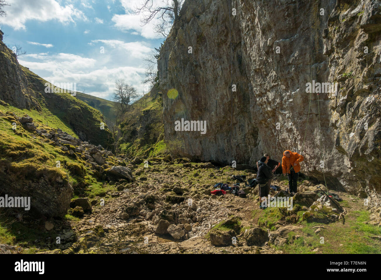 Men socialising: Rock climbers tying in to a rope on a route in Troller's Gill near Appletreewick, Yorkshire Dales, UK - Stock Image