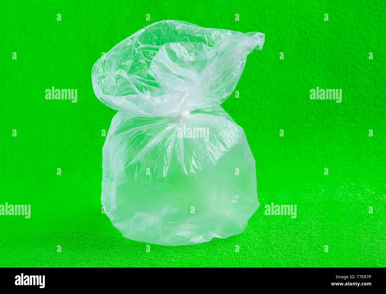 Closed plastic bag on green background. Environmental Protection. - Stock Image