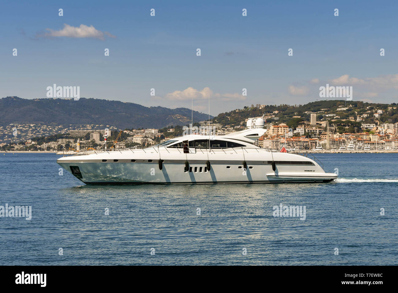 CANNES, FRANCE - APRIL 2019: Luxury motor yacht cruising in the bay in Cannes with the beach and seafront buildings in the background. - Stock Image