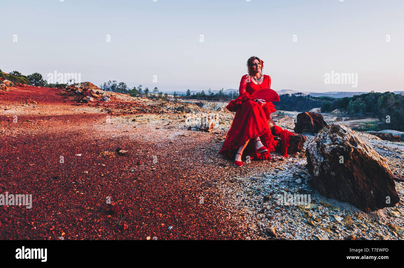 Beautiful woman in red flamenco dress posing on Riotinto mines sitting on a stone - Stock Image