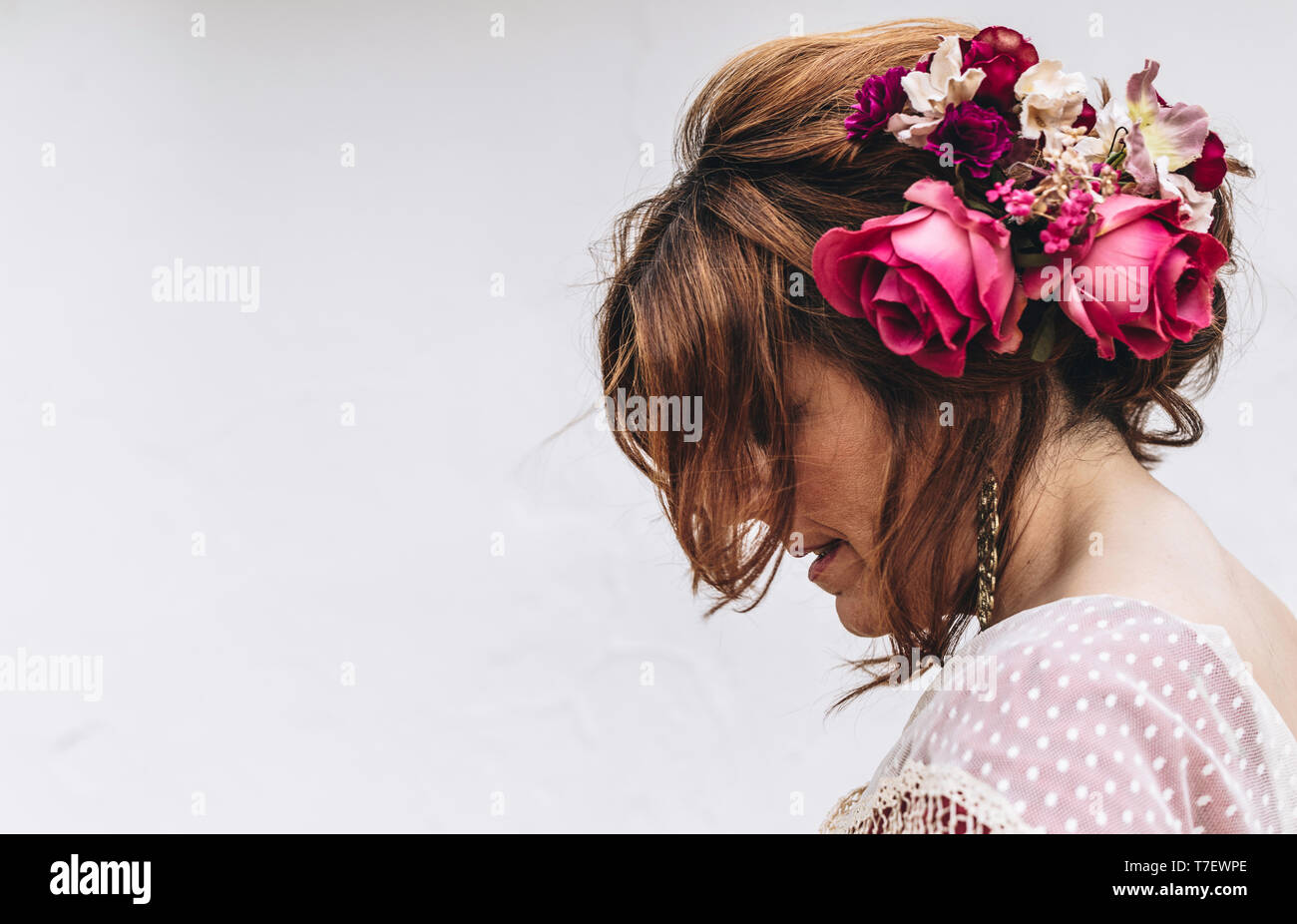 Beauty shot of a flamenco dancer with nice hairstyle and flowers in her hair on white background. April fair 2019 Seville - Stock Image
