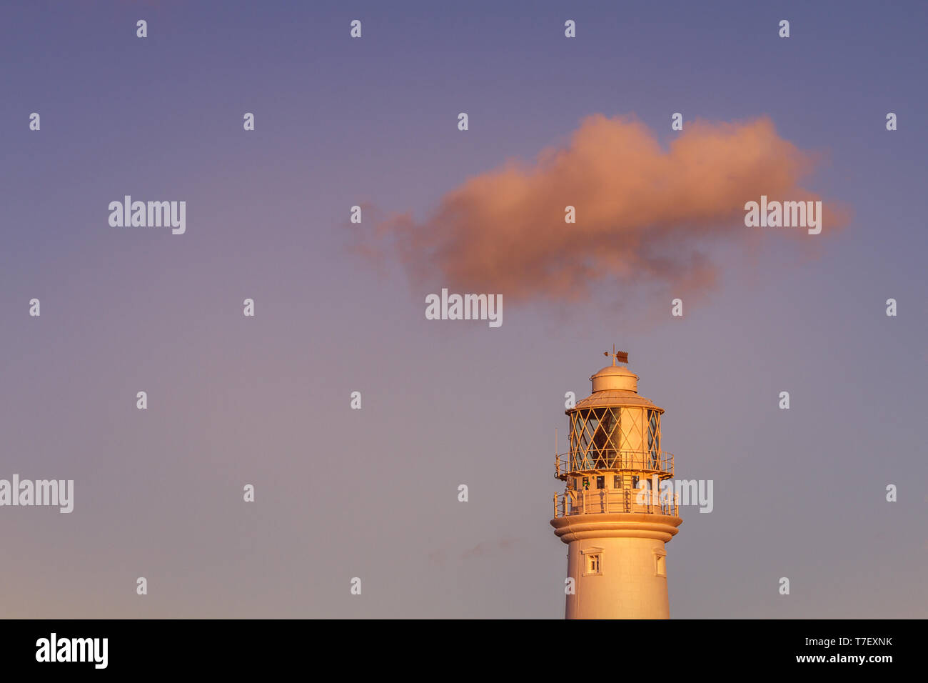 View of Flamborough lighthouse at sunset with a single cloud travelling over the top in blue sky and pink light of the setting sun, East Yorkshire, UK Stock Photo