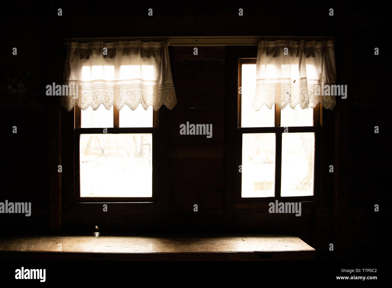 symmetric old windows inside a wood house - Stock Image