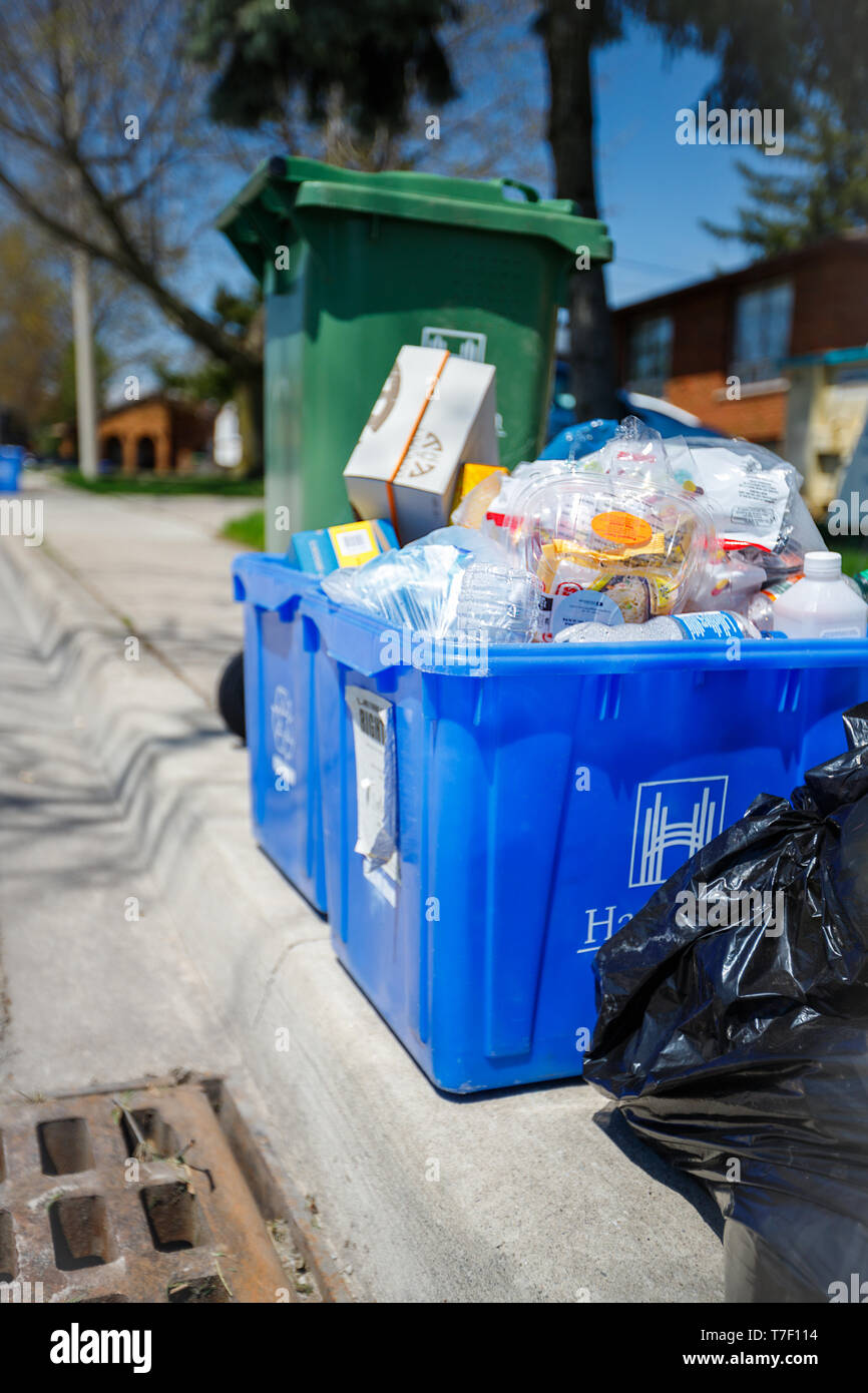 Hamilton, Ontario / Canada - May 2019: Garbage bins with recyclable waste seen at curb side for garbage pick up day in the city - Stock Image