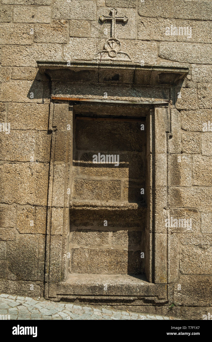 Ornate niche for statue of saint on stone wall of an old church, in a sunny day at Covilha. The town of wool and snow at the Estrela Ridge in Portugal - Stock Image