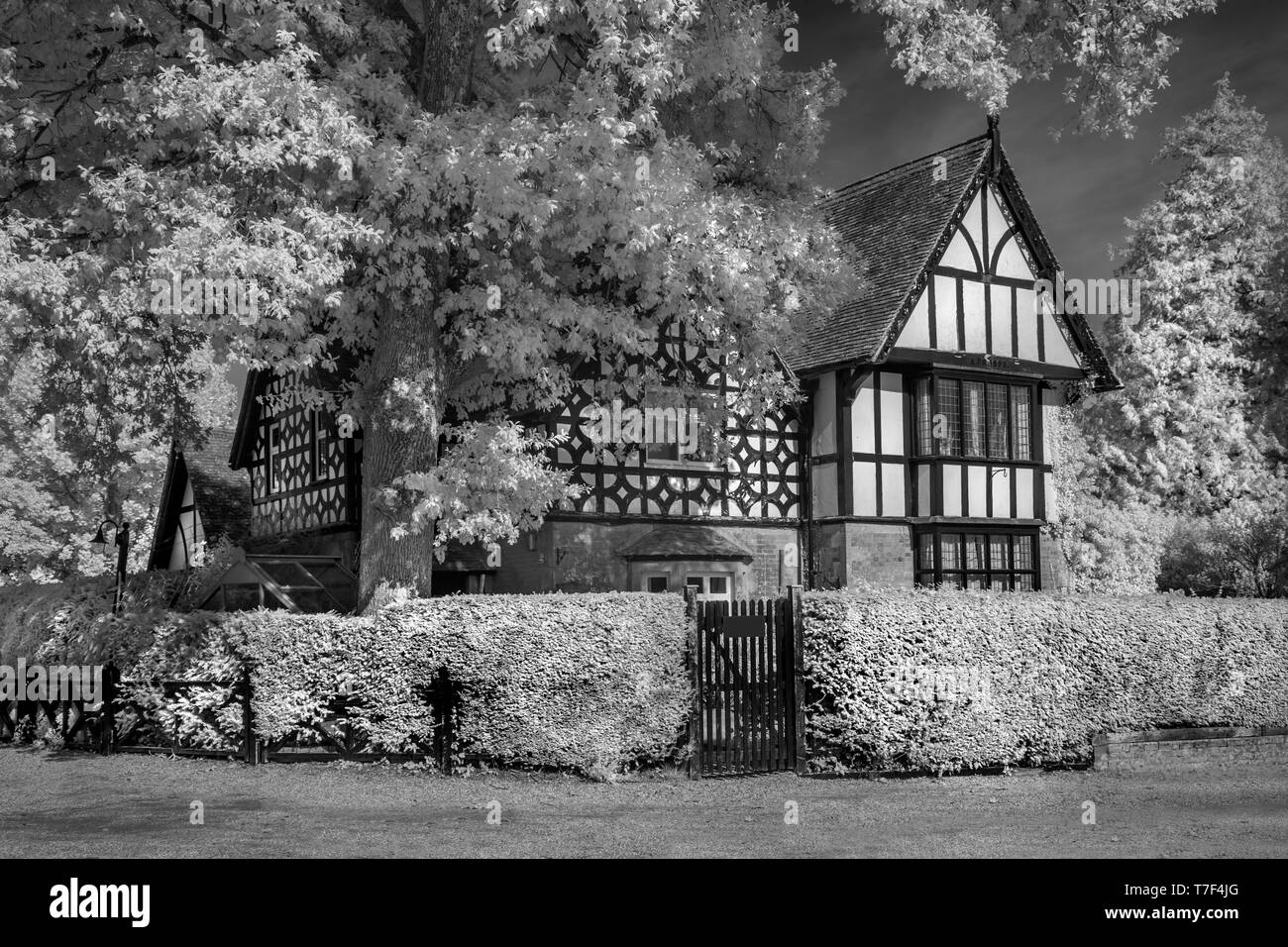 An Infrared image of the Lodge, Larmer Tree Gardens,Tollard Royal, Wiltshire UK. A historic timber framed victorian building. - Stock Image