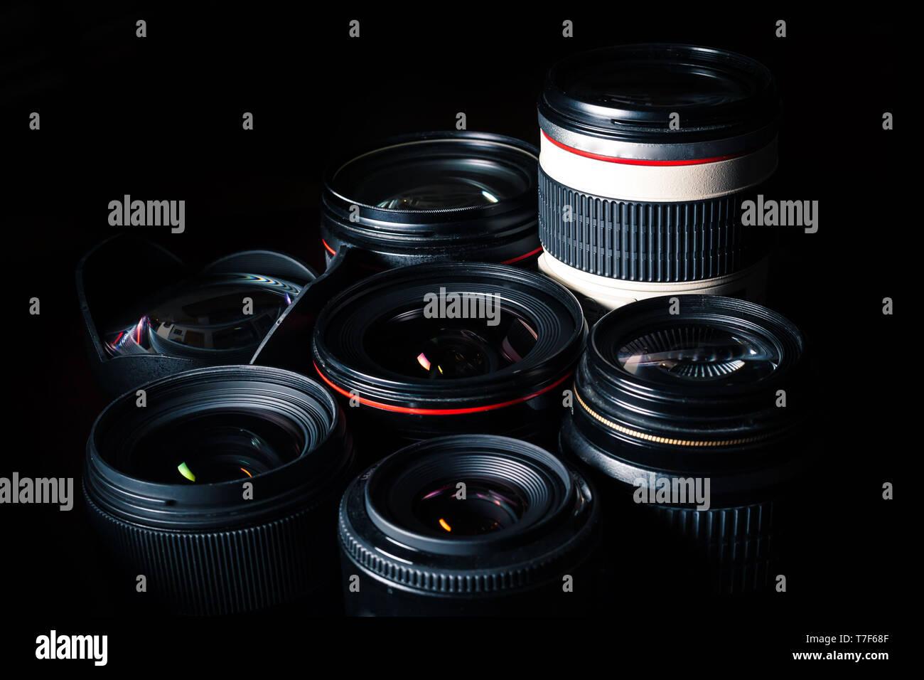 Set of different DSLR lenses on a dark background - Stock Image