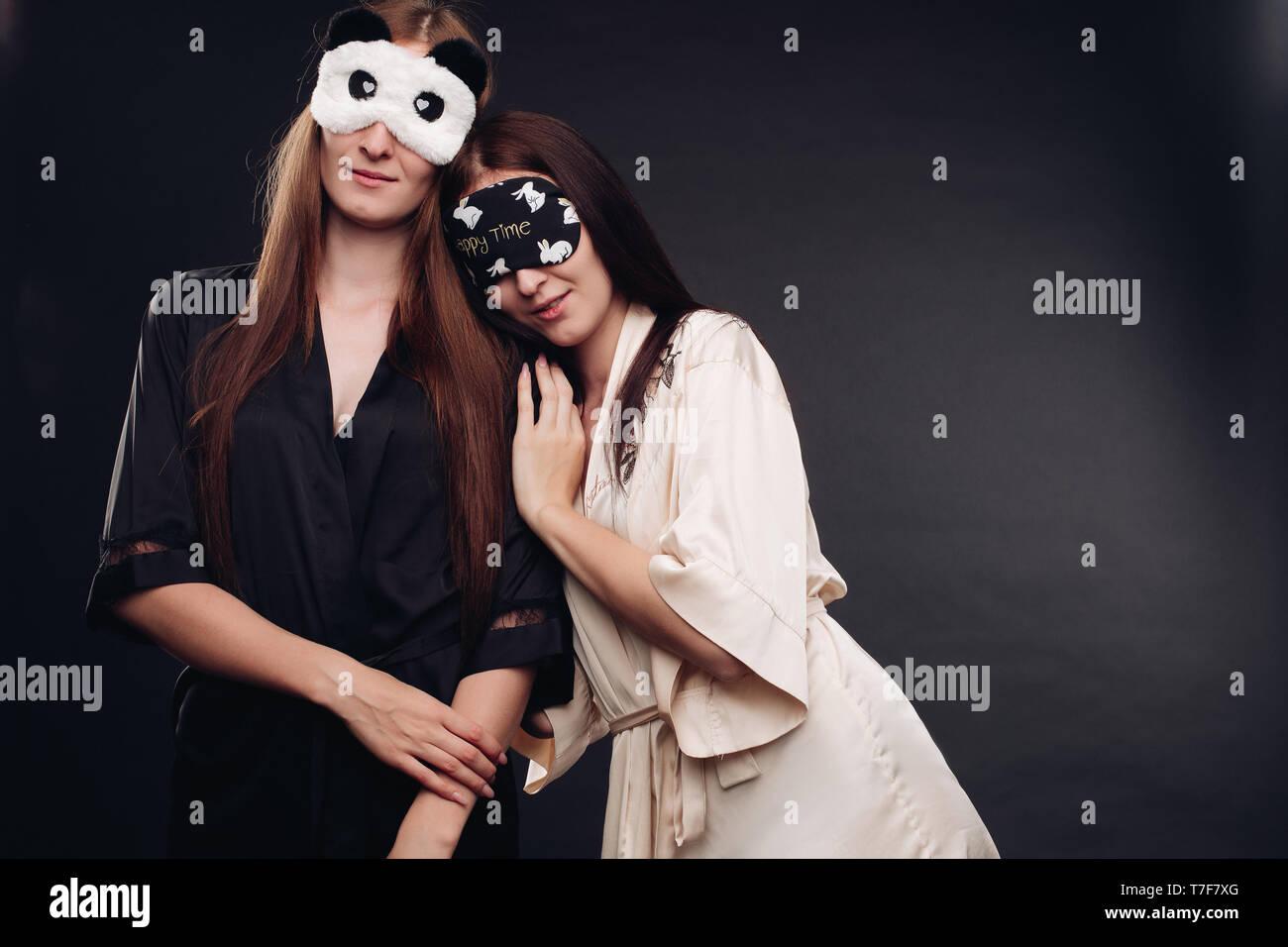 Two young tired girls wearing pajamas sleeping - Stock Image