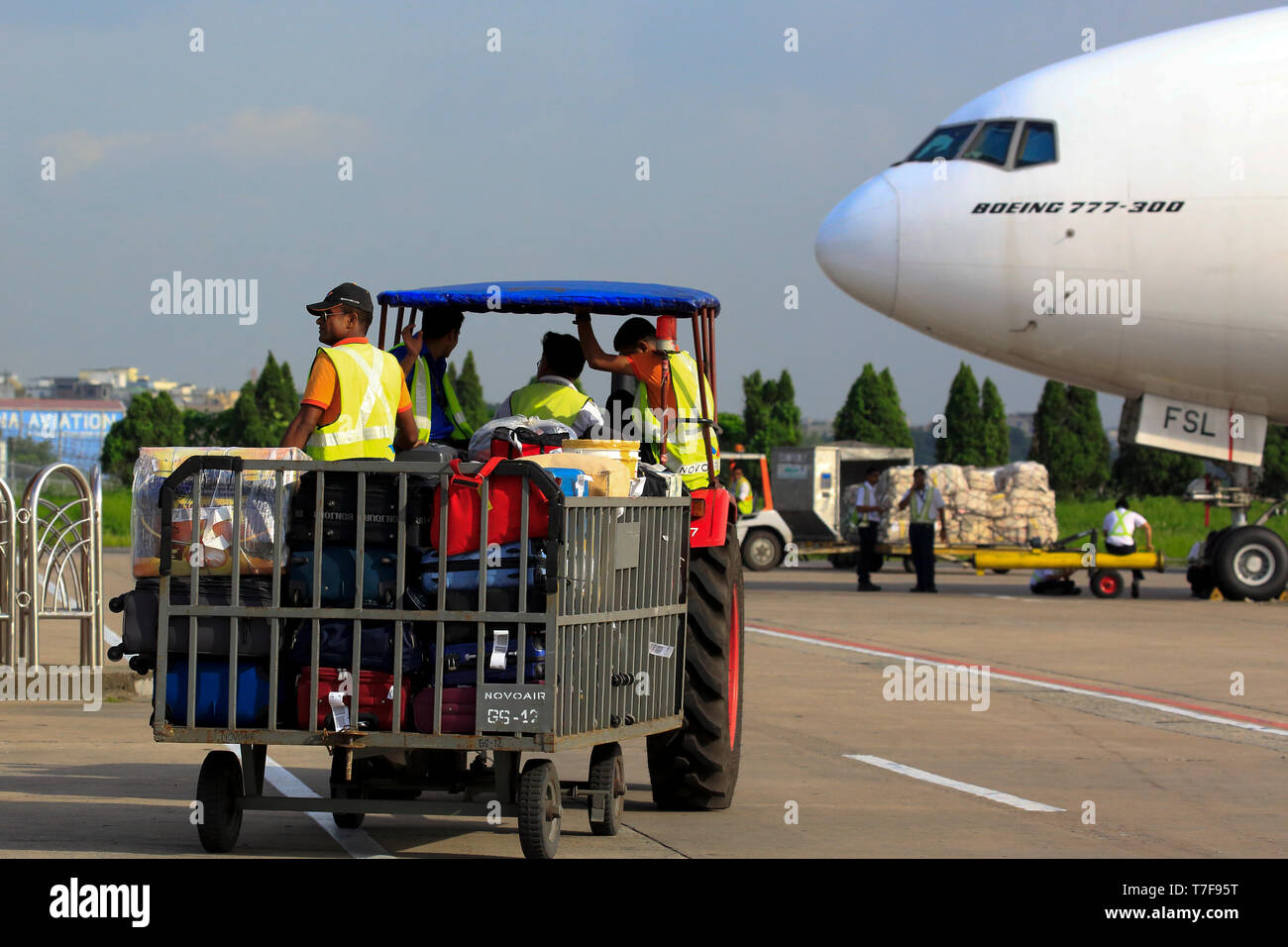 Baggage handler moving luggage at airport airside Hazrat Shahjalal Hazrat Shahjalal International Airport in Dhaka, Bangladesh. Stock Photo