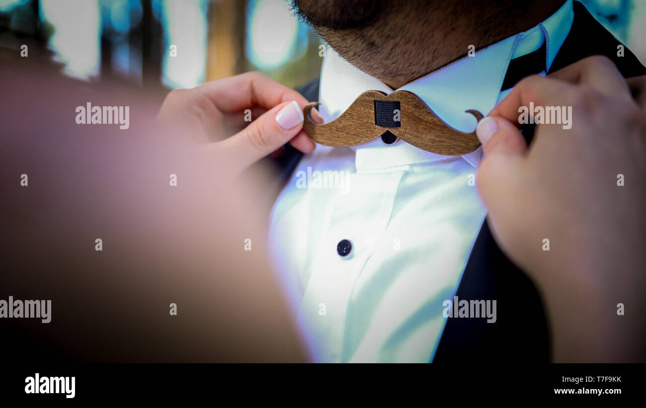 Brides hand on the moustache shaped wooden bowtie of the groom close up view - Stock Image