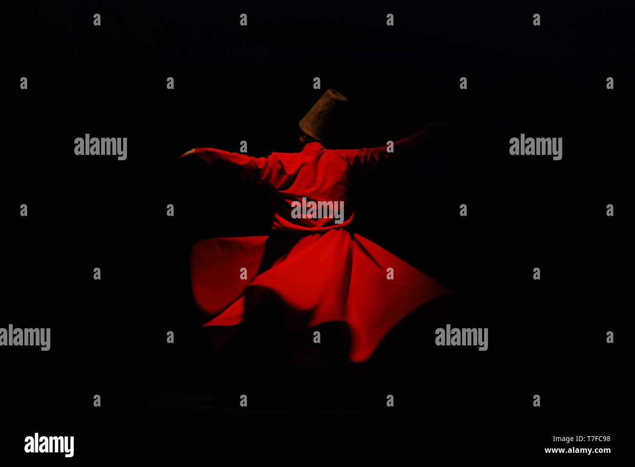Whirling dervish in red garment on black background Stock Photo