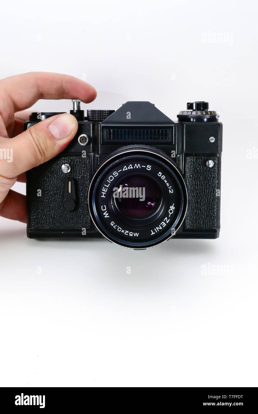 35mm old slr camera on white isolated background hands on - Stock Image