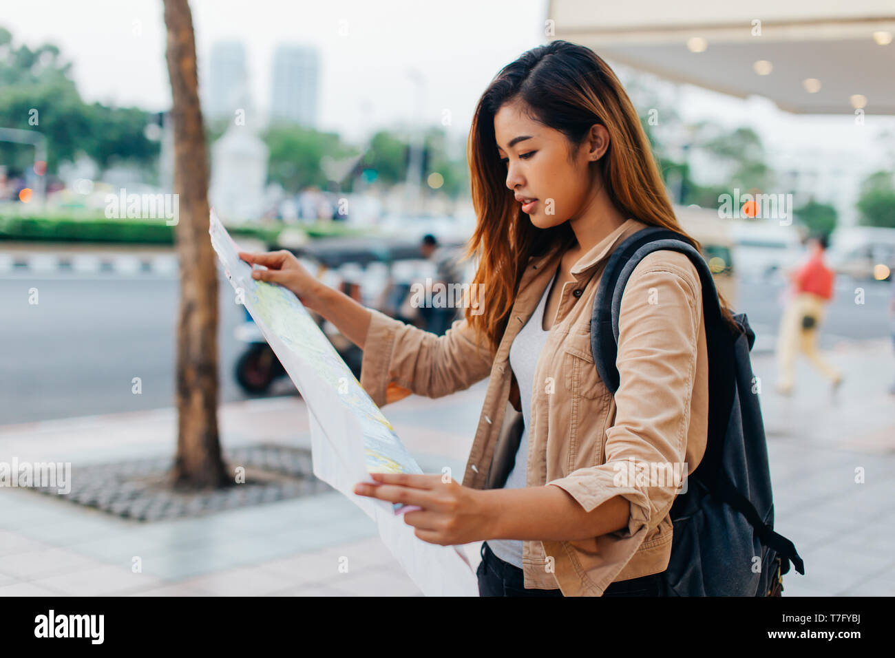 Pretty casual Asian woman with backpack reading paper map while exploring city of Bangkok, Thailand - Stock Image