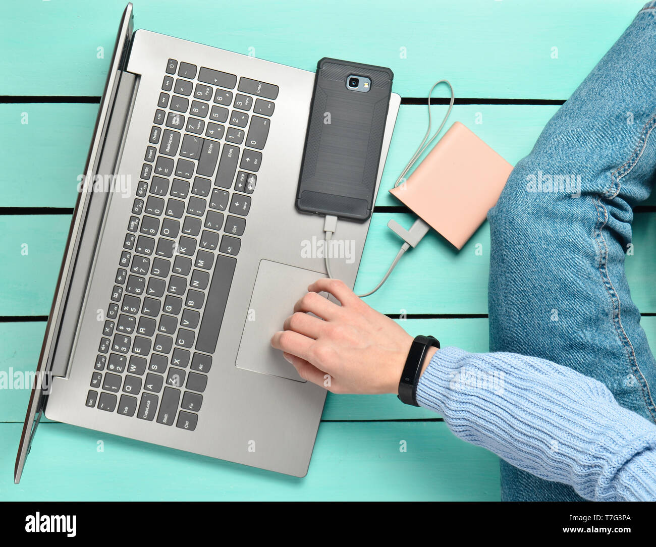 Modern girl sits on a blue wooden floor and uses a laptop. Generation z. The concept of freelancing. Working space. Top view. - Stock Image