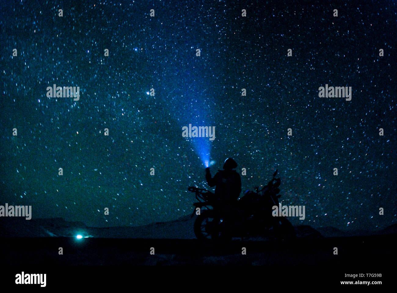 Biker under stars in winter spiti - himalayas in india Stock Photo