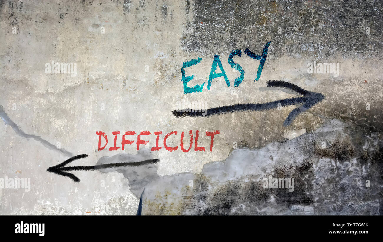 Wall Graffiti the Direction Way to Easy versus Difficult - Stock Image