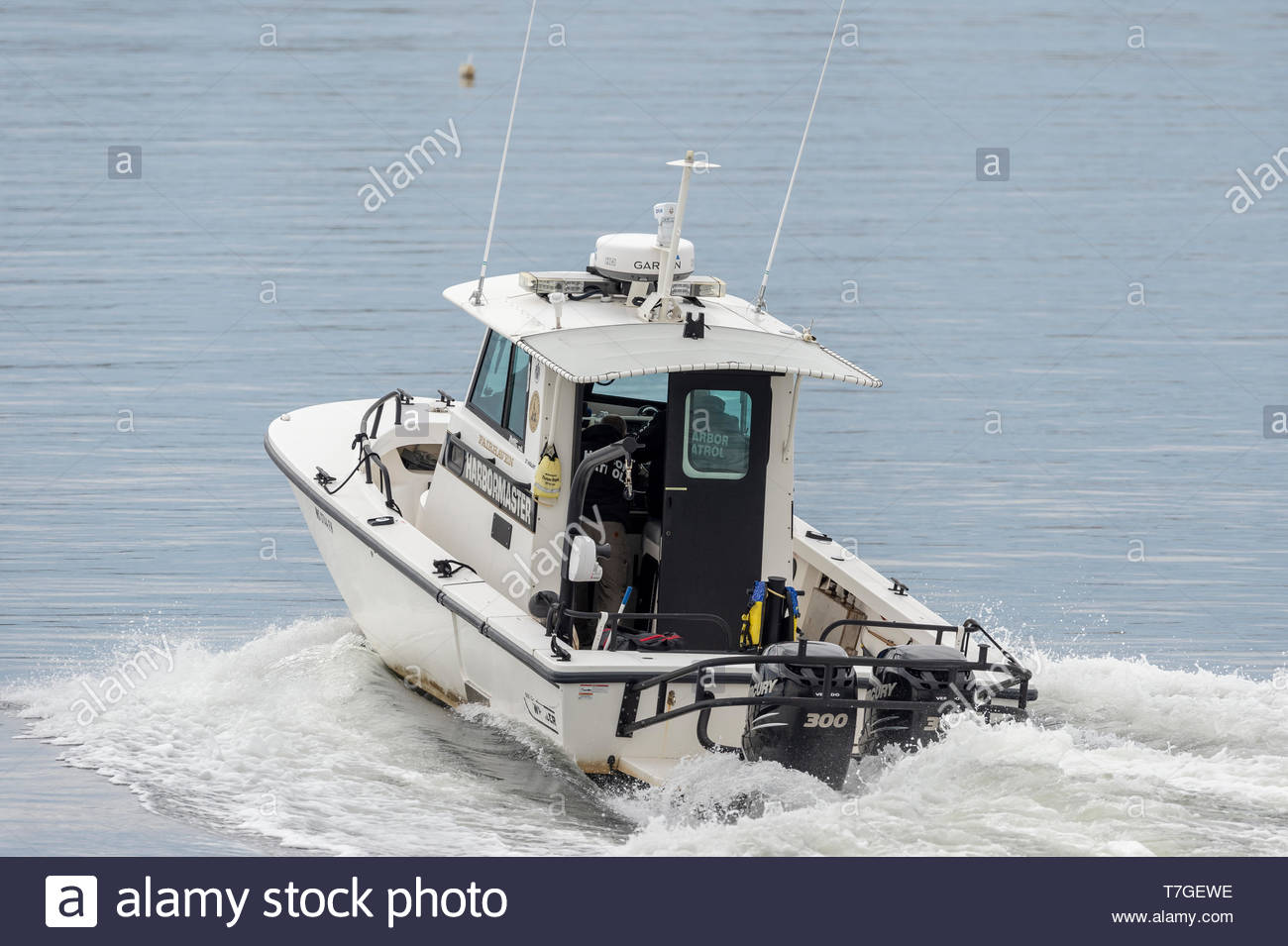 Fairhaven, Massachusetts, USA - May 1, 2019: Patrol boat surges ahead as Fairhaven Harbormaster transits New Bedford hurricane protection barrier - Stock Image