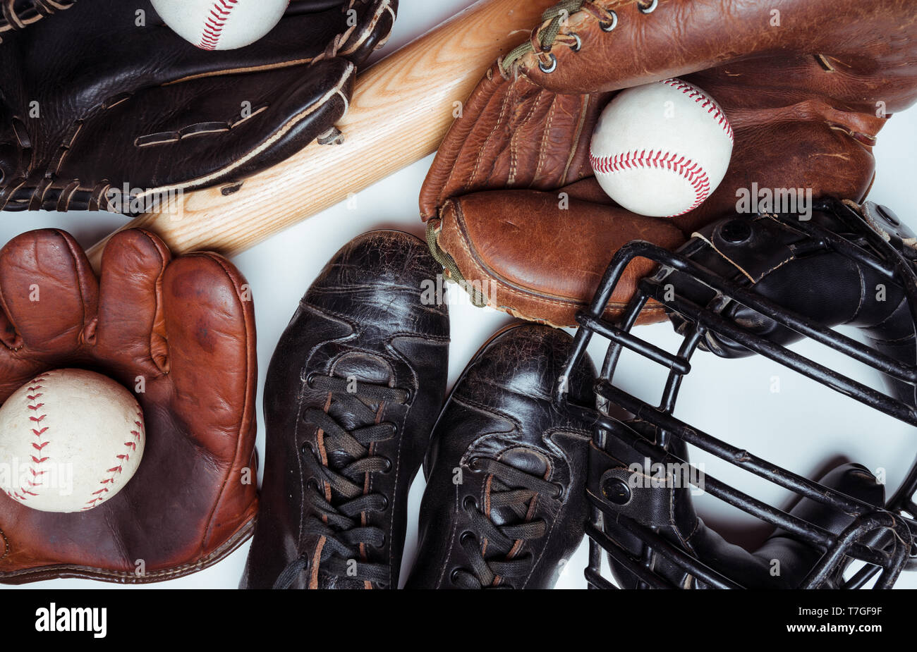 Vintage and modern baseball equipment including bats, balls gloves and face mask on a white background - Stock Image
