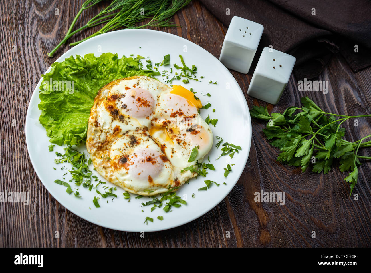 Flat lay of tasty breakfast over grey concrete table background. Fried eggs, micro greens, fresh tomatoes in plate, top view. Clean eating, dieting - Stock Image
