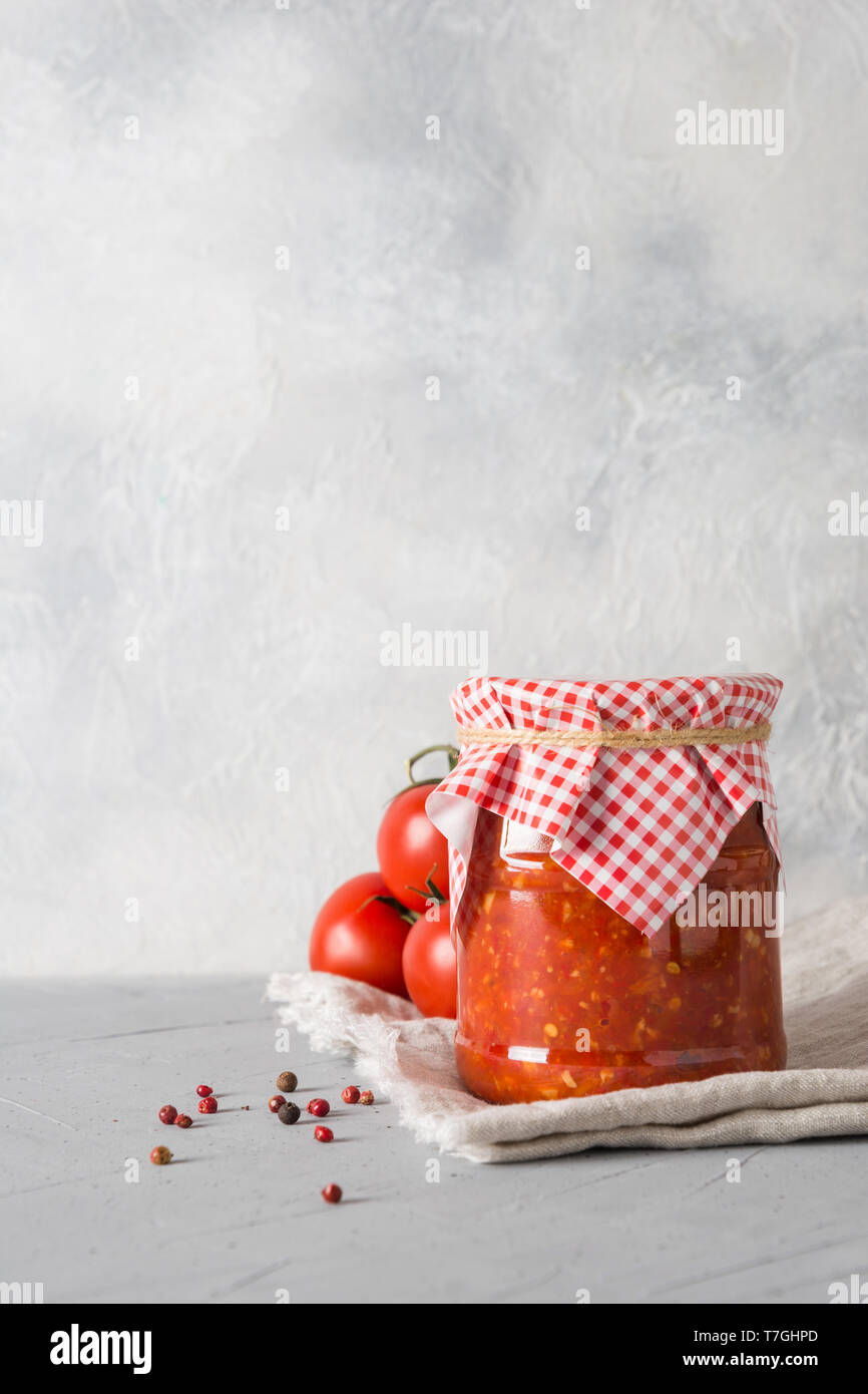Homemade vegetable traditional Maghrebi adjika with hot chili pepper sauce and tomatoes in jar on light background. Paste harissa. Tunisia and Arabic  Stock Photo