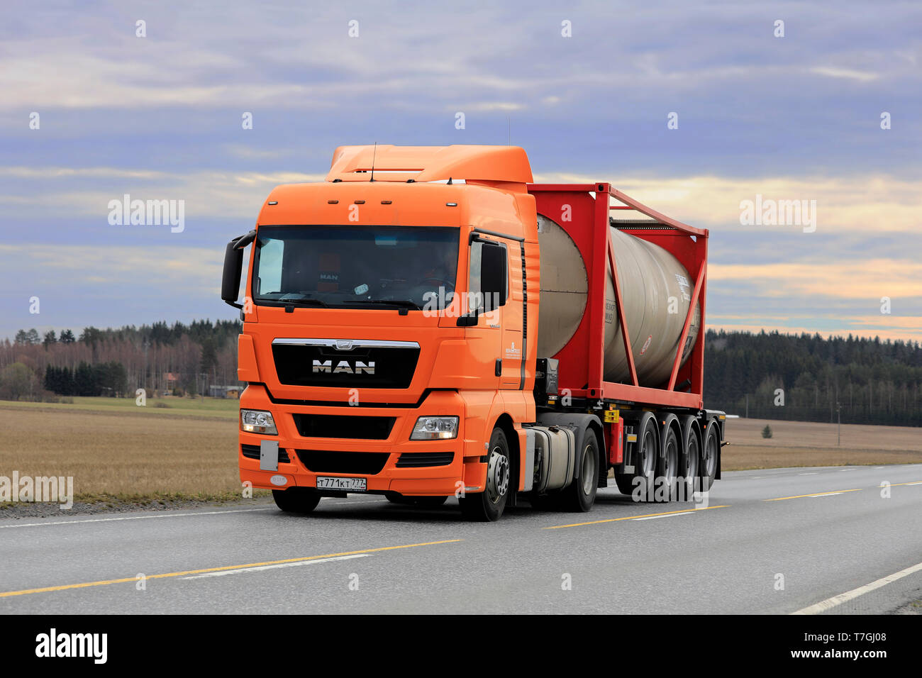 Jokioinen, Finland - April 22, 2019: Orange MAN TGX 18.440 truck transports bulk liquid container along highway 2 in South of Finland. - Stock Image