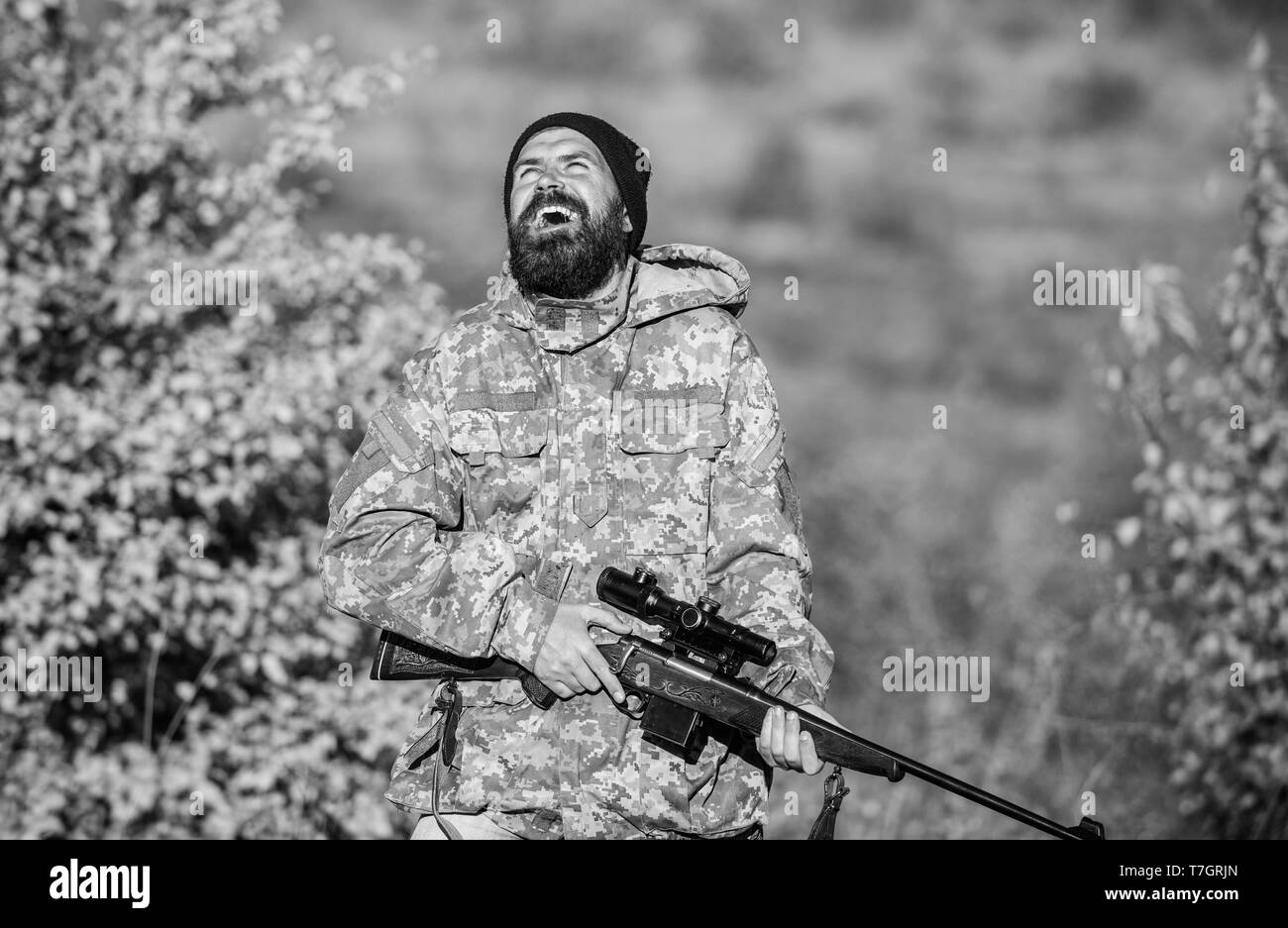 Man brutal gamekeeper nature background. Regulation of hunting. Hunter hold rifle. Bearded hunter spend leisure hunting. Focus and concentration of experienced hunter. Hunting masculine hobby concept. - Stock Image