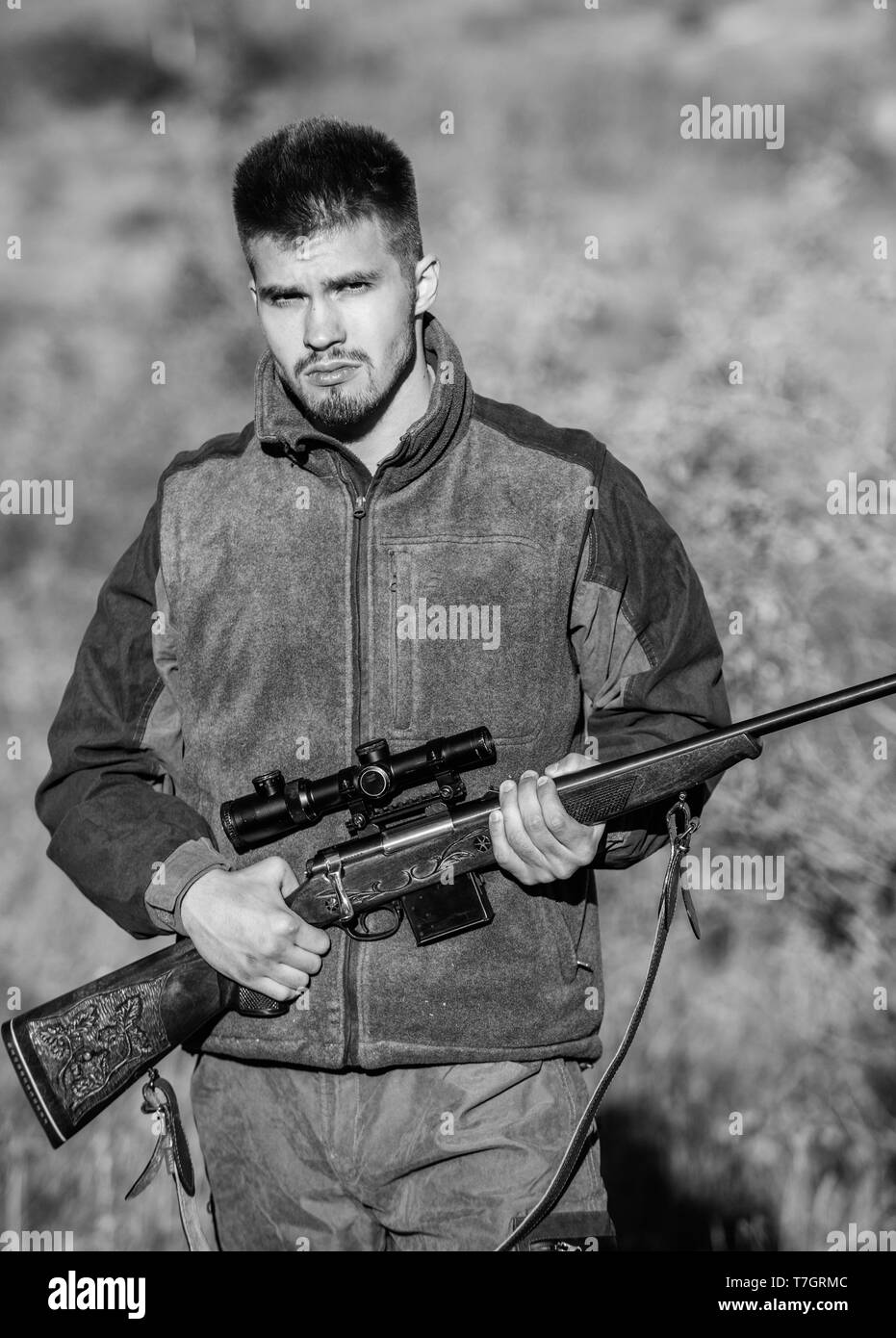Bearded serious hunter spend leisure hunting. Man brutal unshaved gamekeeper nature background. Hunting permit. Hunter hold rifle. Hunting is brutal masculine hobby. Hunting and trapping seasons. - Stock Image