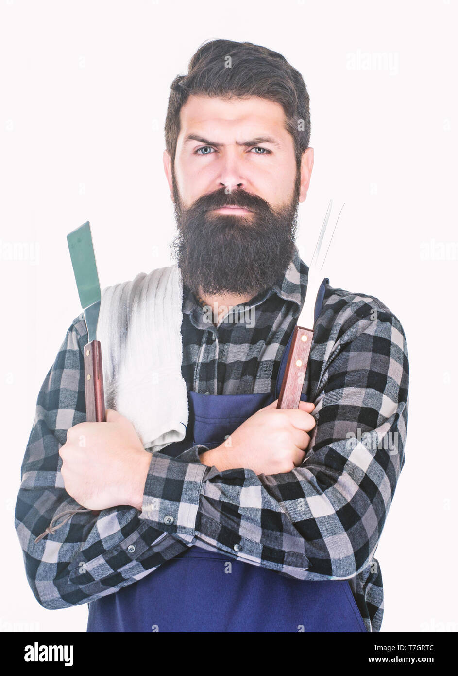 Bearded hipster wear apron for barbecue. Roasting and grilling food. Man hold cooking utensils barbecue. Tools for roasting meat outdoors. Picnic and barbecue. Cooking meat in park. Masculine hobby. - Stock Image