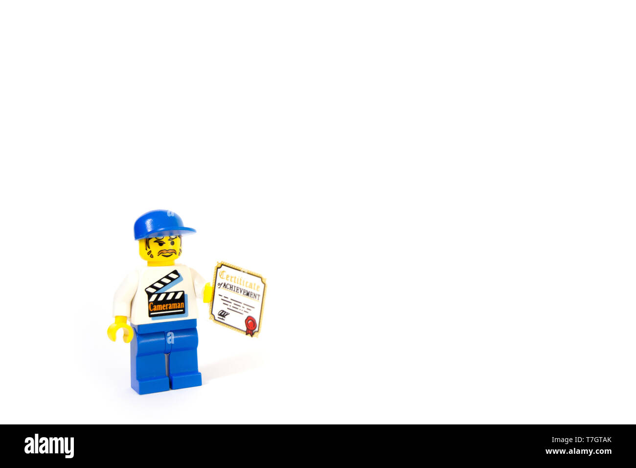 A LEGO film maker holding a certificate of Achievement, this cameraman progressing his career. - Stock Image