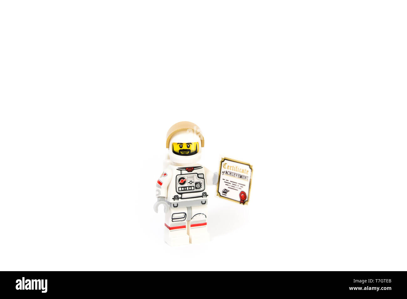 Astronaut holding a certificate of achievement showing his career progression. - Stock Image