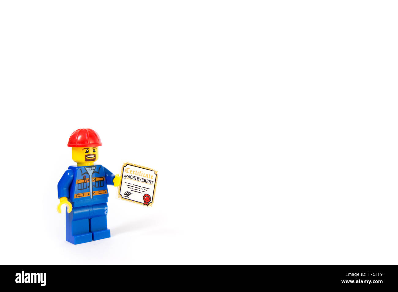 Construction worker holding a certificate of achievement. - Stock Image