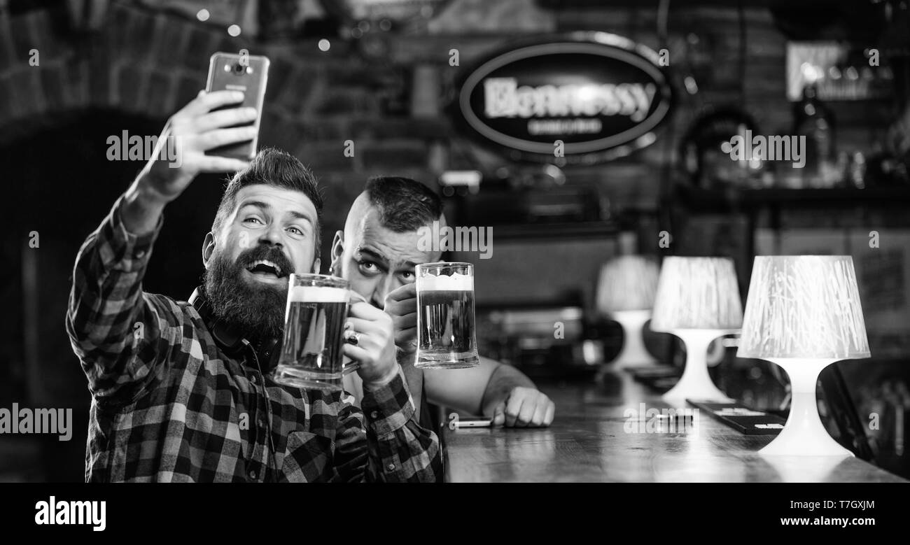 Taking selfie concept. Send selfie to friends social networks. Man in bar drinking beer. Take selfie photo to remember great evening in pub. Online communication. Man bearded hipster hold smartphone. - Stock Image