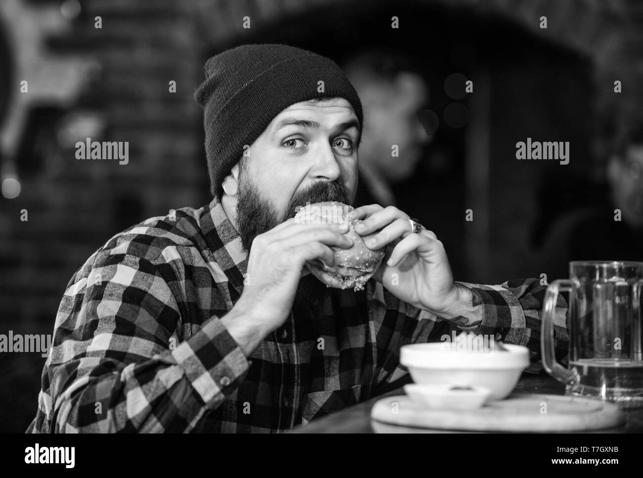 Brutal hipster bearded man sit at bar counter. High calorie food. Cheat meal. Delicious burger concept. Enjoy taste of fresh burger. Hipster hungry man eat burger. Man with beard eat burger menu. - Stock Image