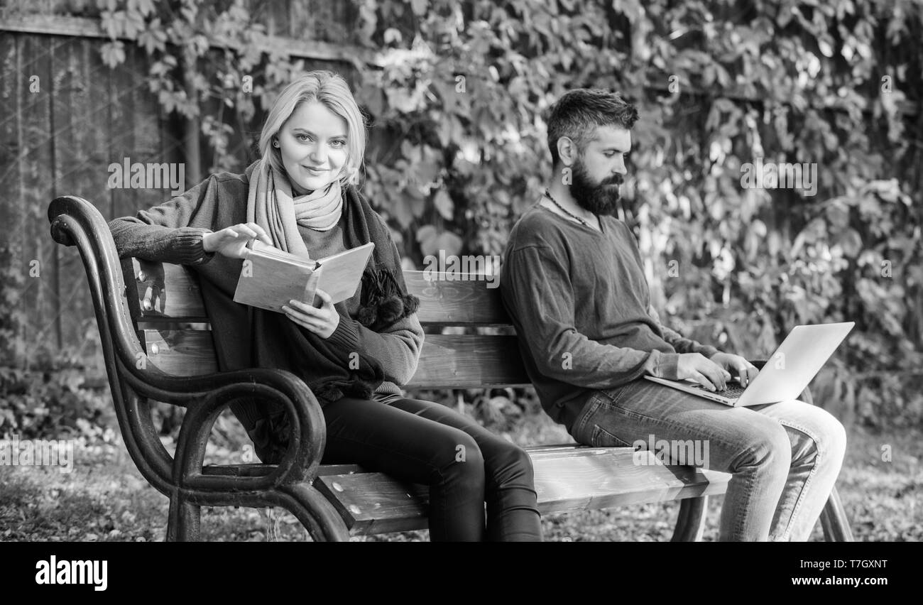 Digital against paper. education and learning. Education and technology. Online education and learning. man and woman with book and notebook in park. Spending nice time in spring park. Surfing net. - Stock Image
