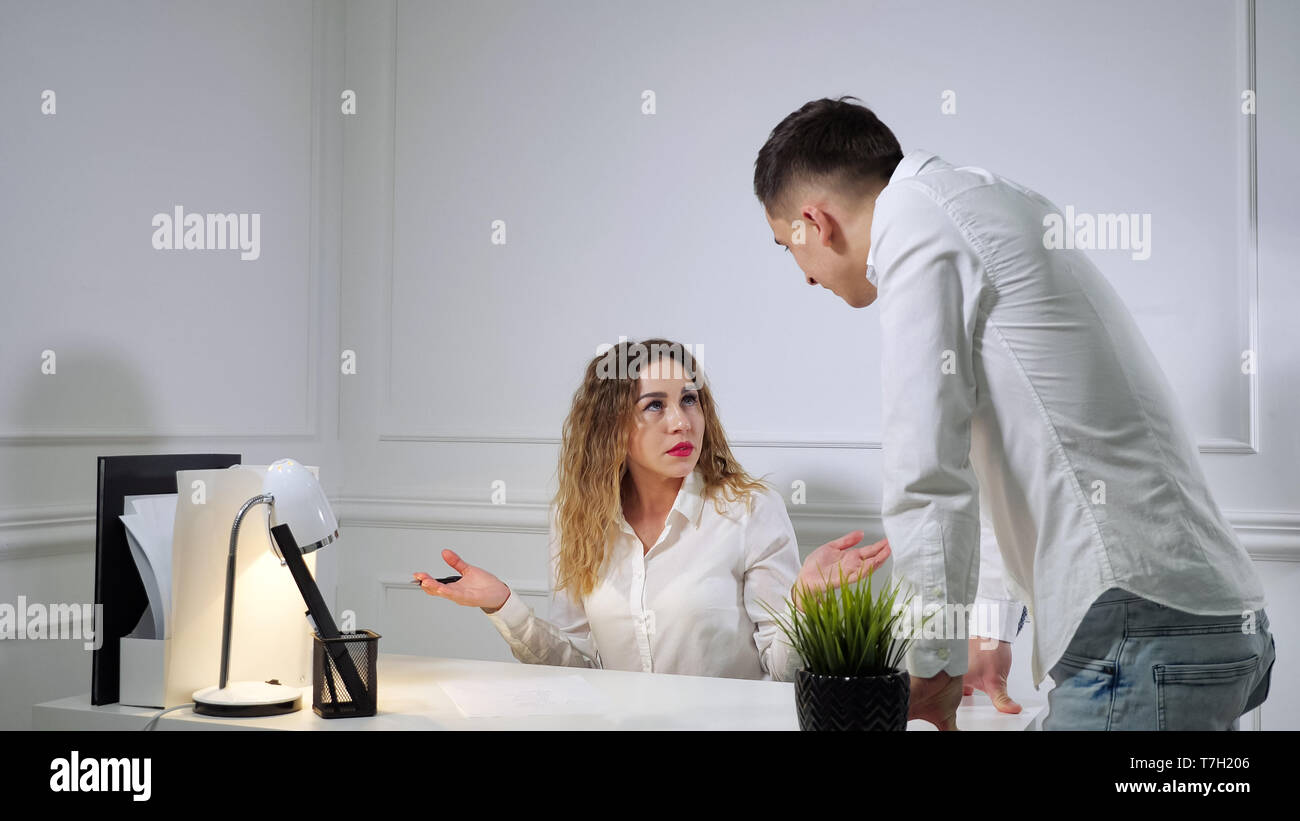 Colleagues man and woman in uniform dress code are quarreling with each other in their office workplace. Man comes to the table and makes claims to woman. - Stock Image