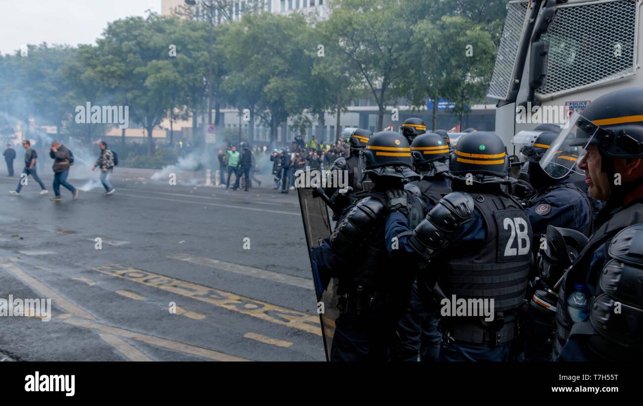 Policiers formant un barrage contre les manifestants sous les gaz lacrymogène à Paris le 1er Mai 2019 - Stock Image