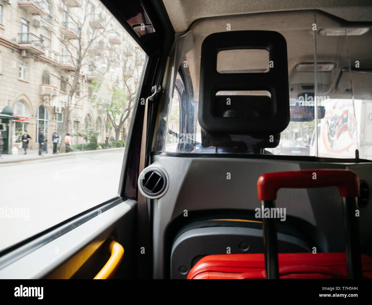 Defocused view from hackney carriage taxi cab in Baku Azerbaijan with red luggage inside and street view with people silhouette - Stock Image