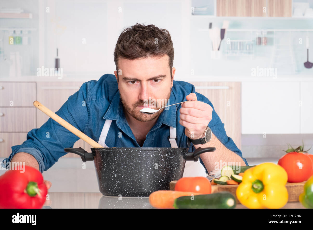 Concentrated young man preparing food at home - Stock Image