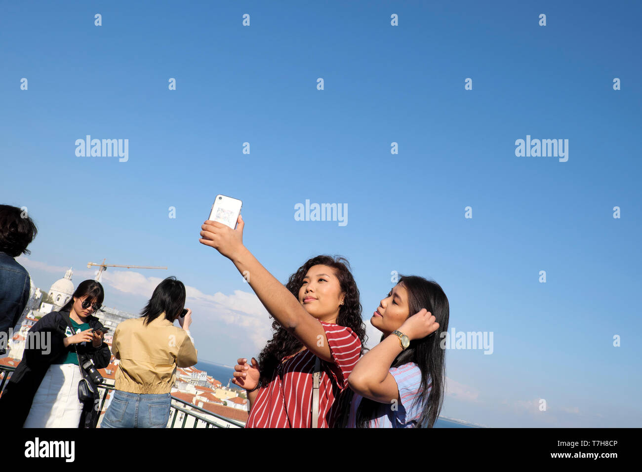 Beautiful young woman with friend taking selfie with mobile phone with background of Alfama district of Lisbon in Portugal Europe EU  KATHY DEWITT Stock Photo