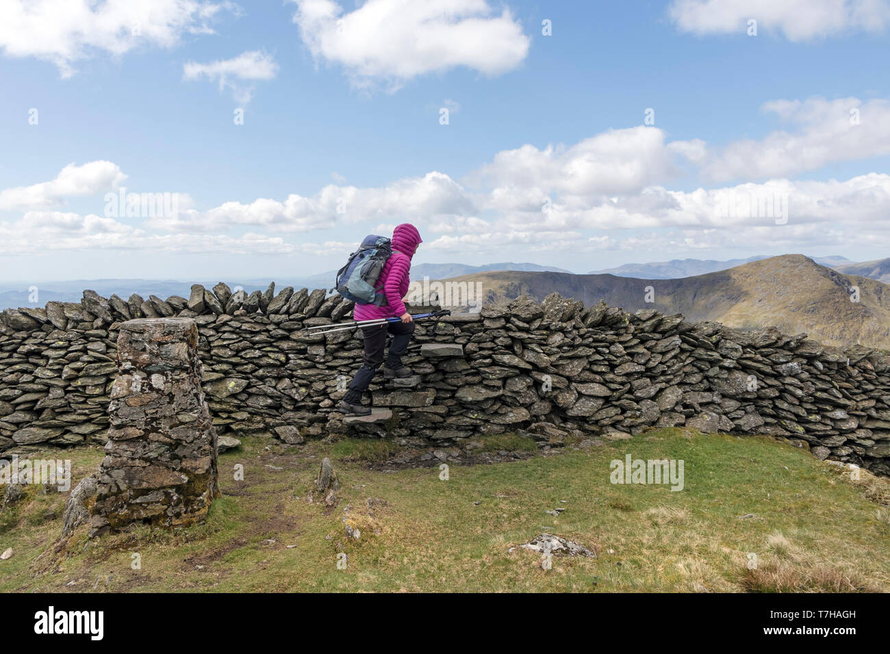 Walker Climbing the Stile Next to the Trig Point on the Summit of Kentmere Pike with the View West Lake District, Cumbria, UK Stock Photo