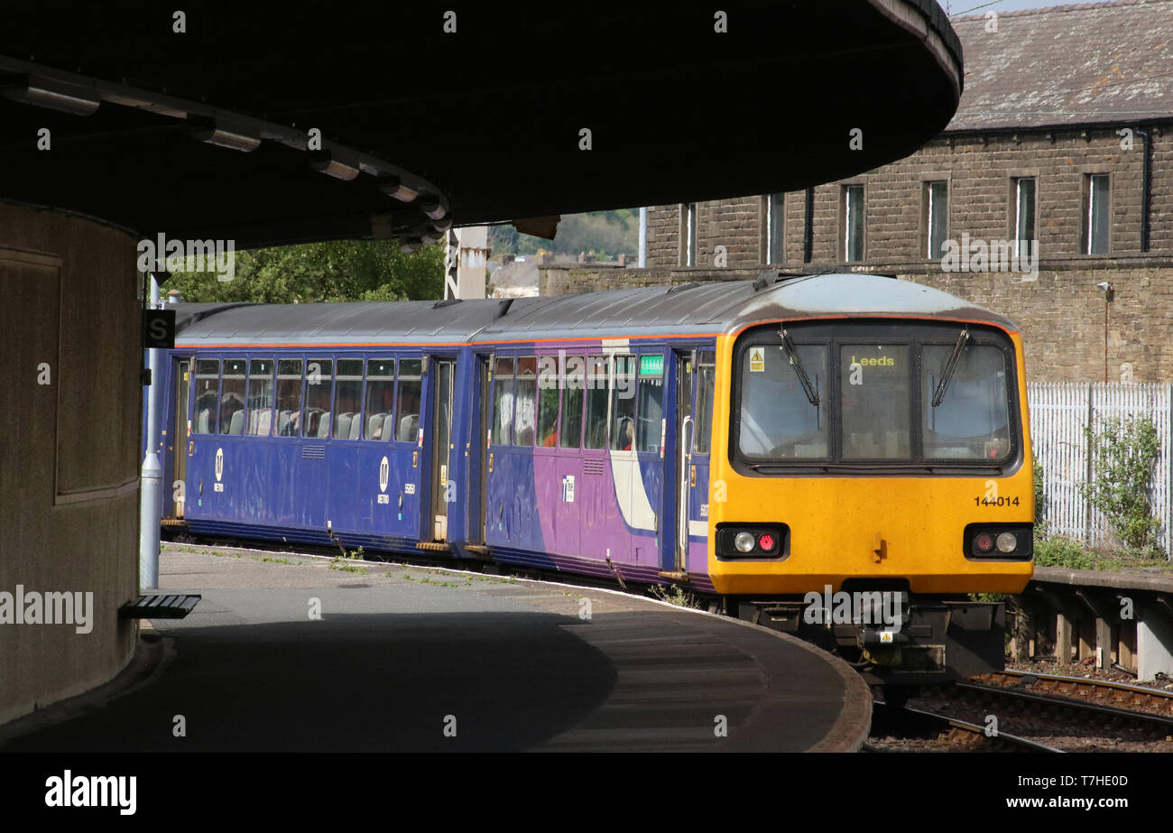 Class 144 Pacer diesel multiple unit number 144014 in Northern livery leaving platform 2 at Carnforth railway station on 6th May 2019. - Stock Image