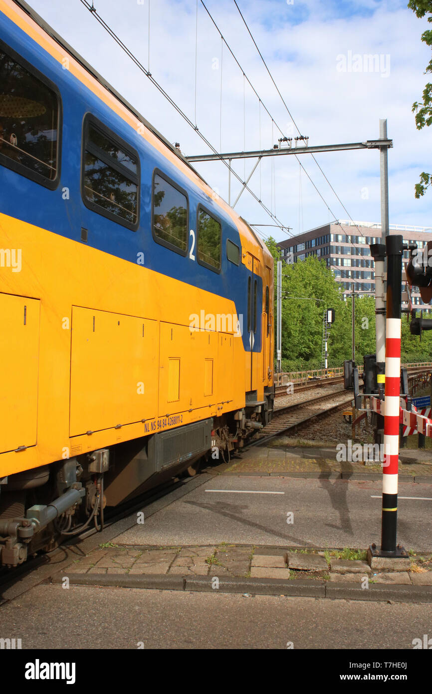 Dutch railways multiple unit train in NS blue and yellow livery on a level crossing in Leiden on Thursday 25th April 2019. - Stock Image
