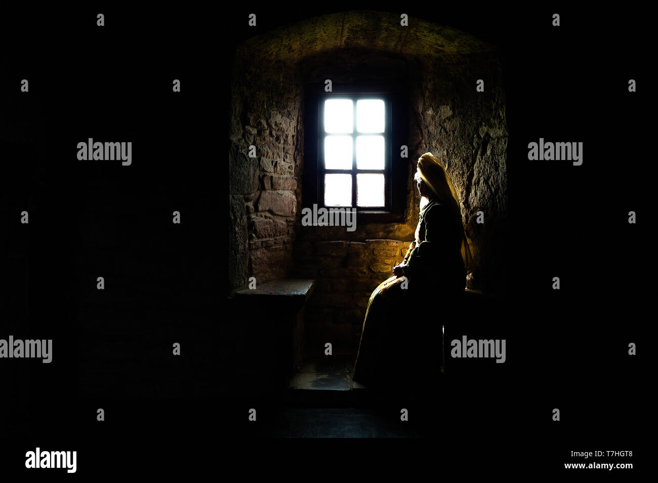 Partial silhouette of a woman in medieval dress sitting in the dark looking out of a bright window in the depths of an ancient castle Stock Photo