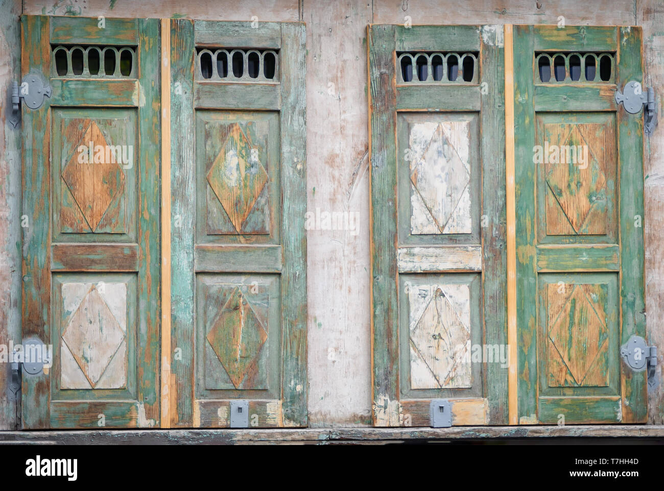 Old vintage wooden windows shutters. Yellow and green tones. Details - Stock Image