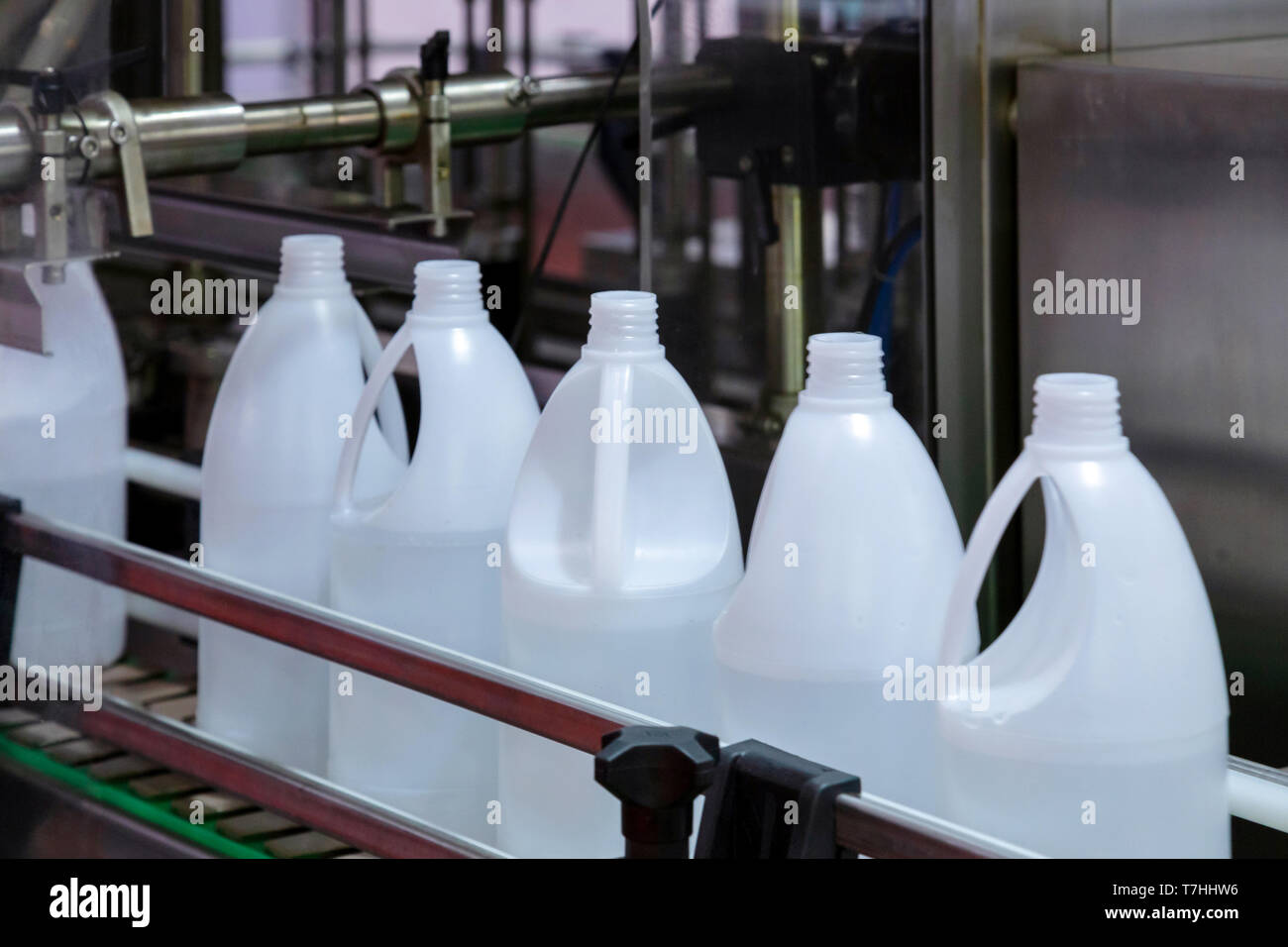 white plastic gallons or bottle on the production line of the conveyor at filling machine in the factory. selective focus. industrial and technology c - Stock Image