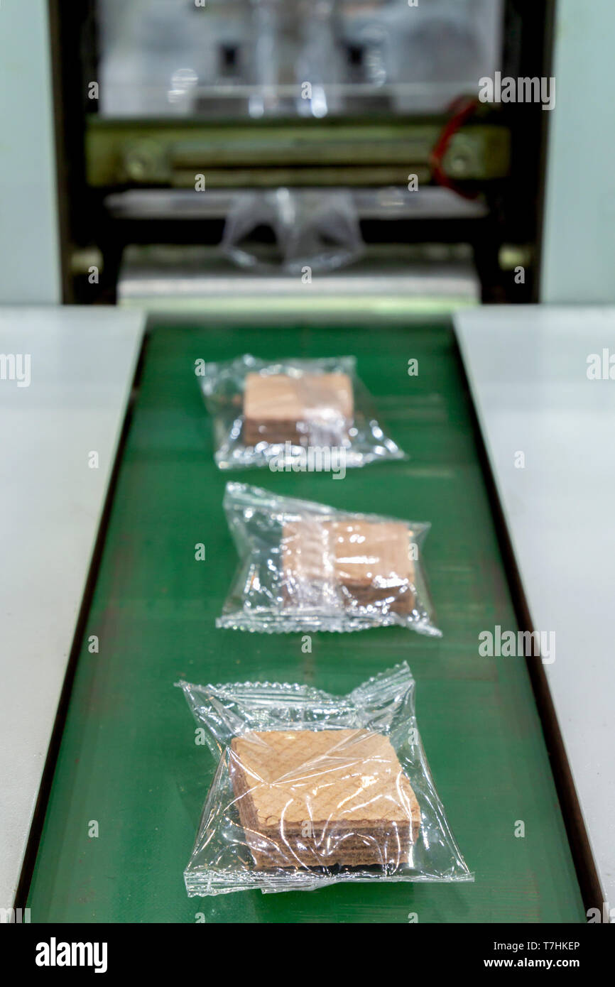 crispy wafer biscuits packing in the plastic back in production line on the conveyor belt of automatic packing machine at bakery factory. food industr - Stock Image