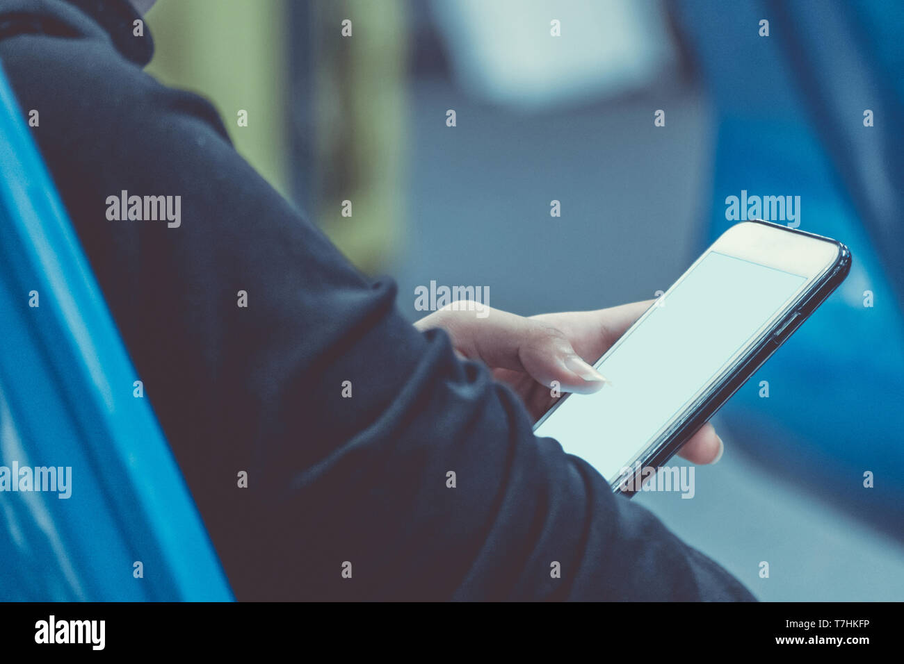woman holding and using mobile smartphone to connect airport wifi internet to searching for information while waiting for flight at the airport termin - Stock Image