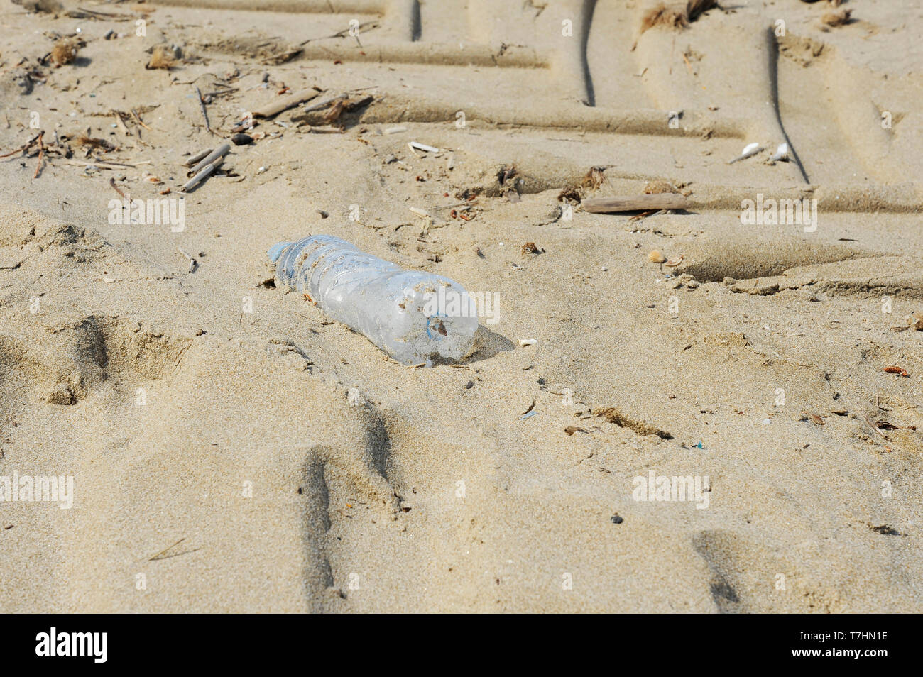 Plastic bottle on the sand. Garbage on the beach. Dirty sea shore. Environmental pollution. Save the Planet. Ecological problem. Nature theme. - Stock Image